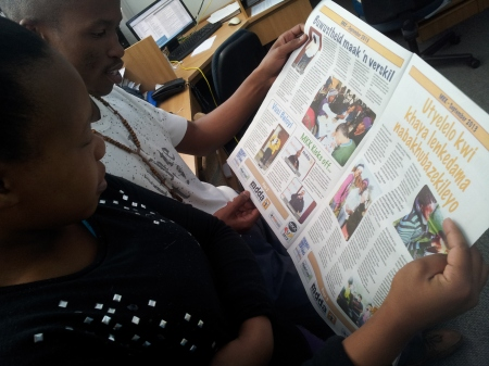 "Bush Radio staff checking out ""Media on the Move"" - the newspaper produced by MKK2013 delegates"
